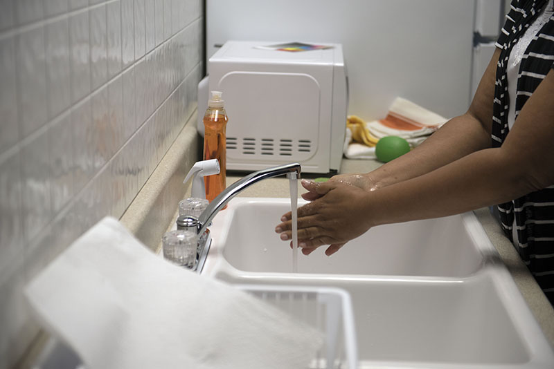 A woman washing her hands with soap at a sink with running water.