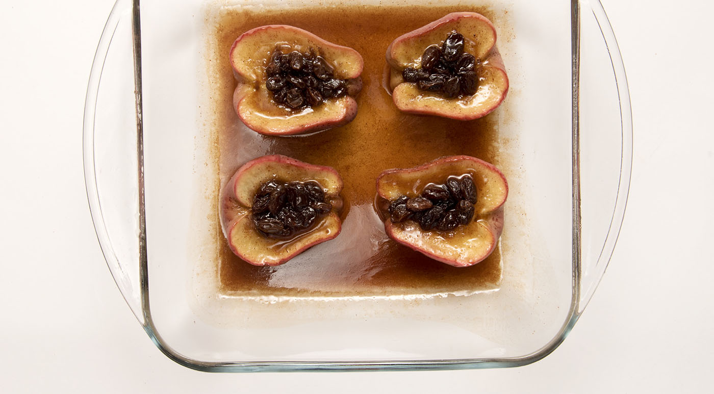 Four baked apples halves with raisins on top of each in a square clear glass baking dish.