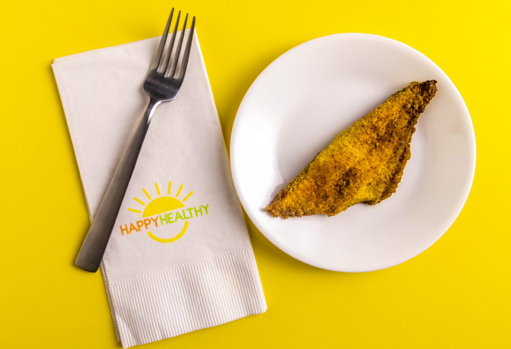 Fork and napkin beside plate with a cooked, seasoned catfish fillet