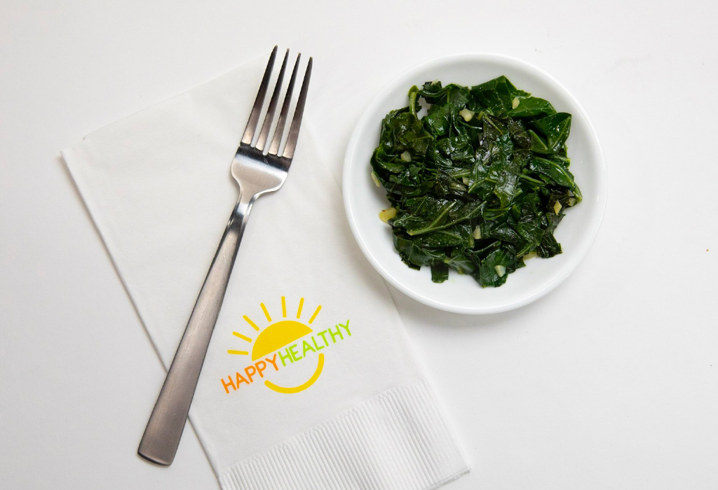 Plate of collard greens beside napkin and fork.