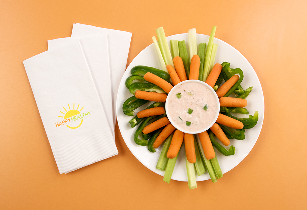 Plated selection of fresh vegetables including baby carrots, celery, and bell peppers surrounding a bowl of sour cream and salsa dip beside a napkin