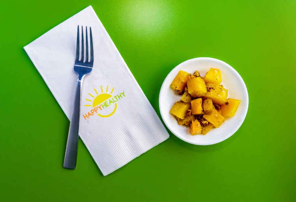 Plate of glazed butternut squash beside napkin and fork.