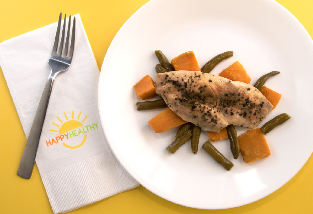 fork, napkin, and plate with a seasoned chicken filet over green beans and sweet potatoes