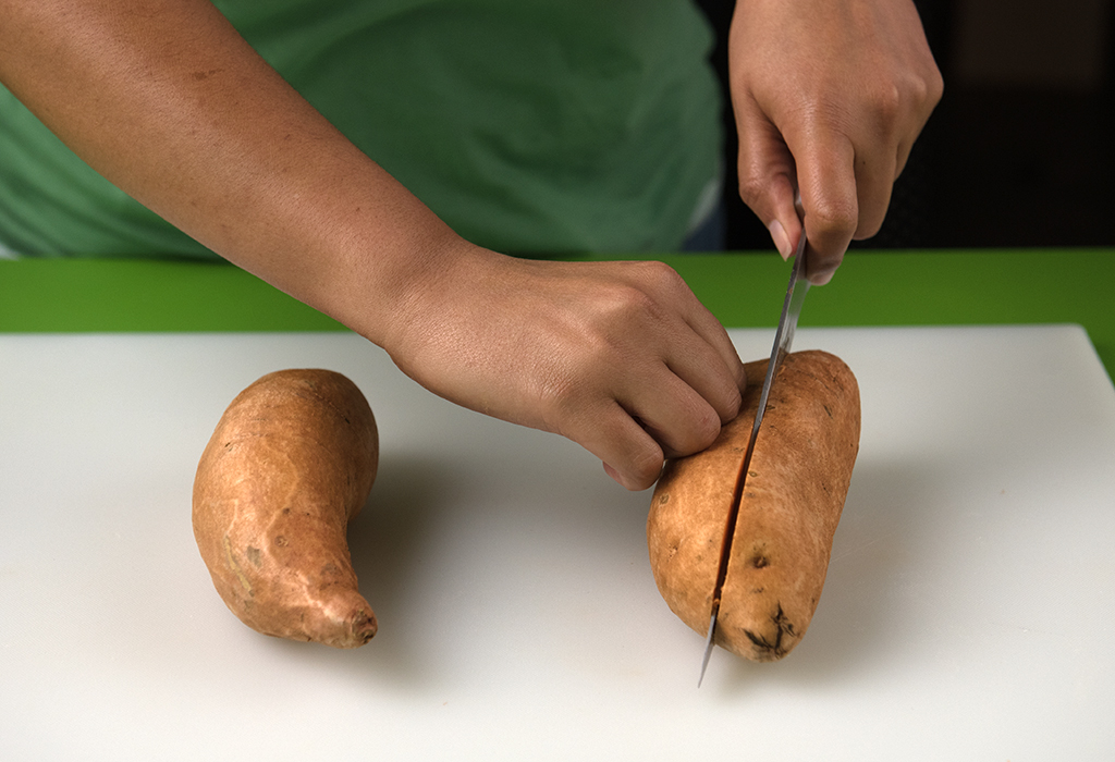 Hands chopping potatoes on chopping board