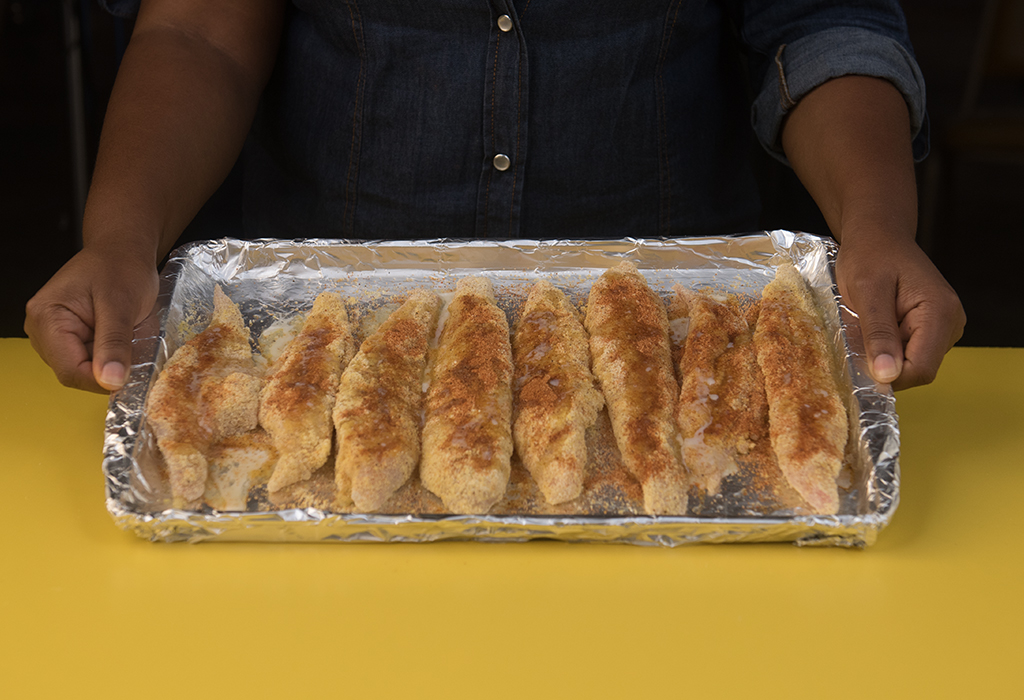 hands holding foil wrapped backing sheet with 8 pieces of seasoned meat