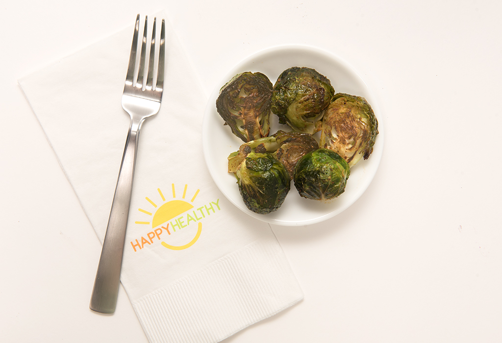 Bowl of roasted brussels sprouts beside napkin and fork