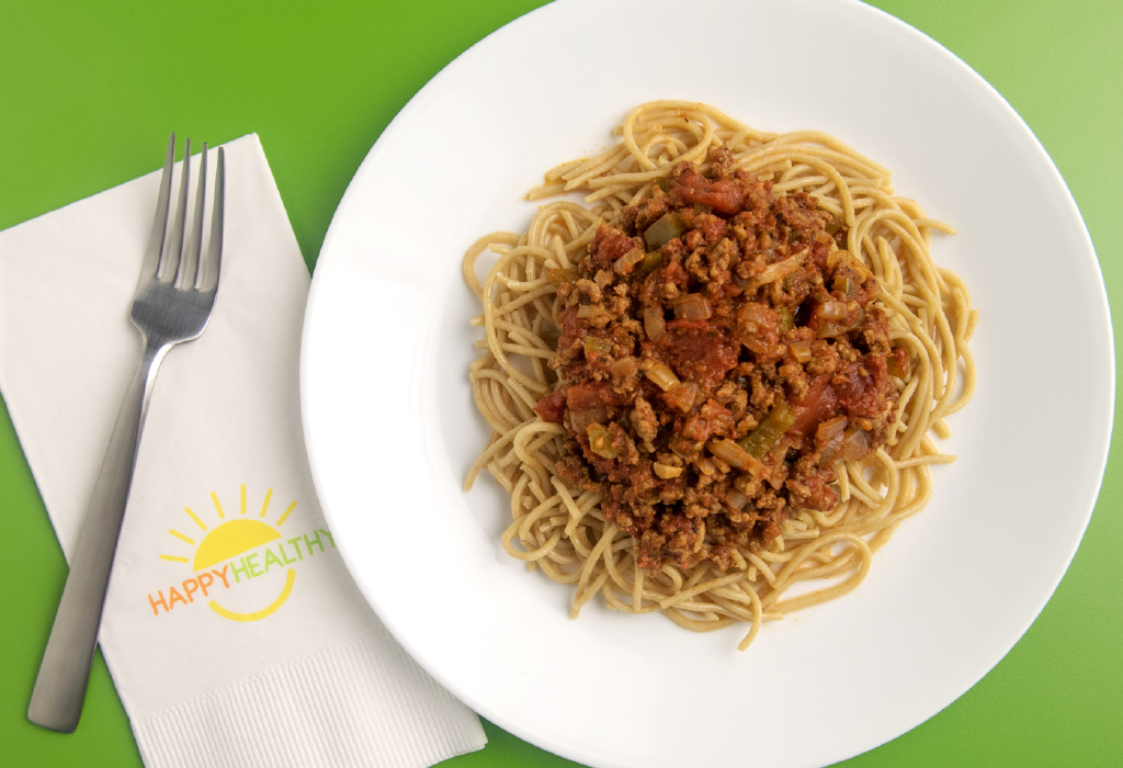 Bowl of spaghetti topped with tomato and meat sauce beside napkin and fork