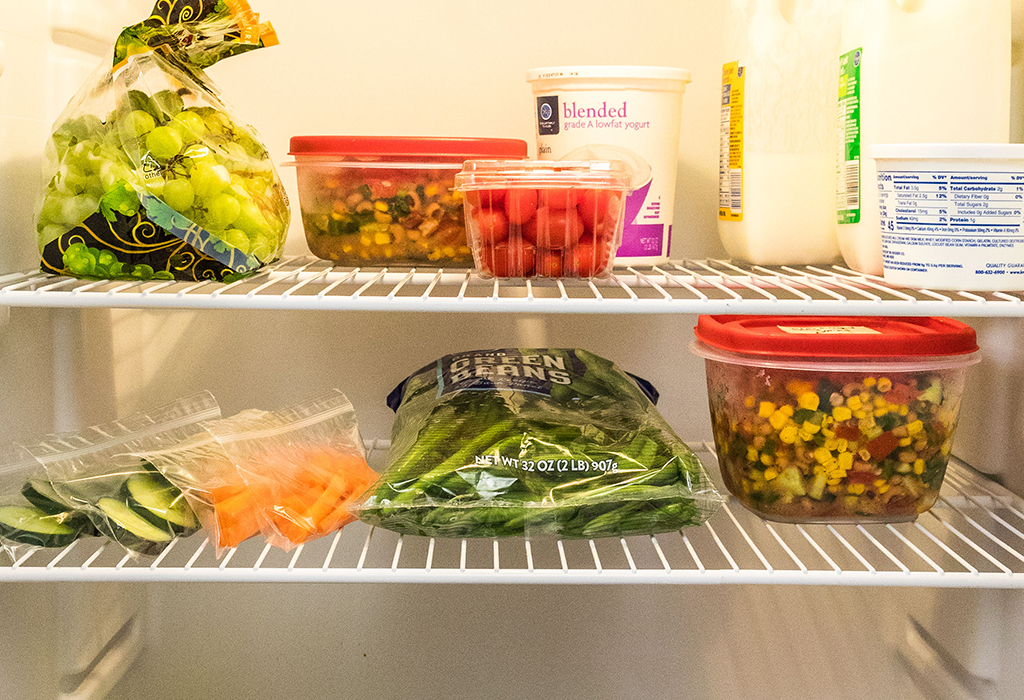 various fruits and vegetables in plastic bags and containers on refrigerator shelves