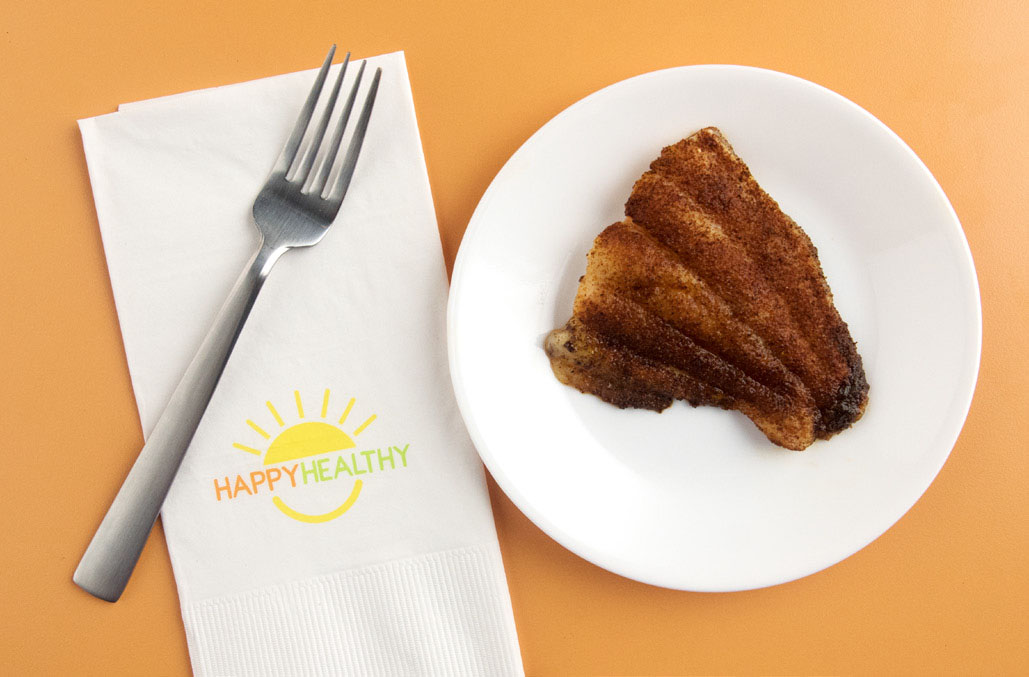 An oven-blackened catfish filet on a saucer with HappyHealthy napkin and fork to the side.
