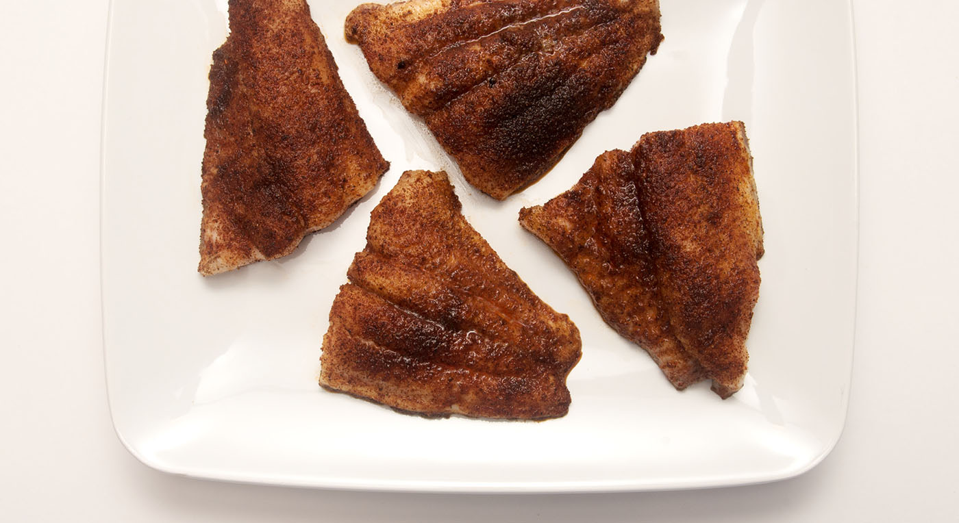 Four pieces of oven blackened catfish on a square, white serving platter.