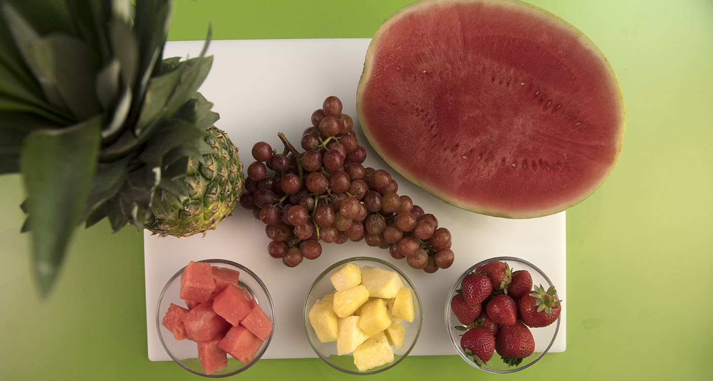 A sliced watermelon, a bunch of grapes, a whole pineapple and a bowl of cubed watermelon, a bowl of cubed pineapple, and a bowl of strawberries on a white cutting board.