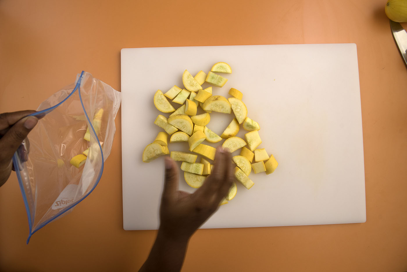 A woman moving cut yellow squash from the cutting board to a storage bag.
