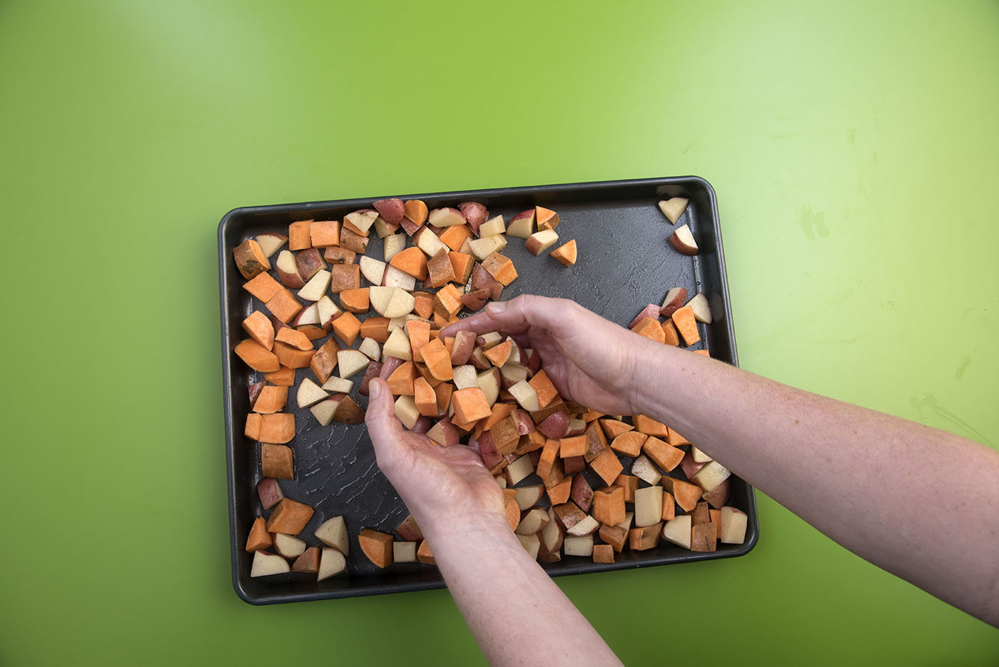 Cubed Irish and sweet potatoes on a baking sheet.