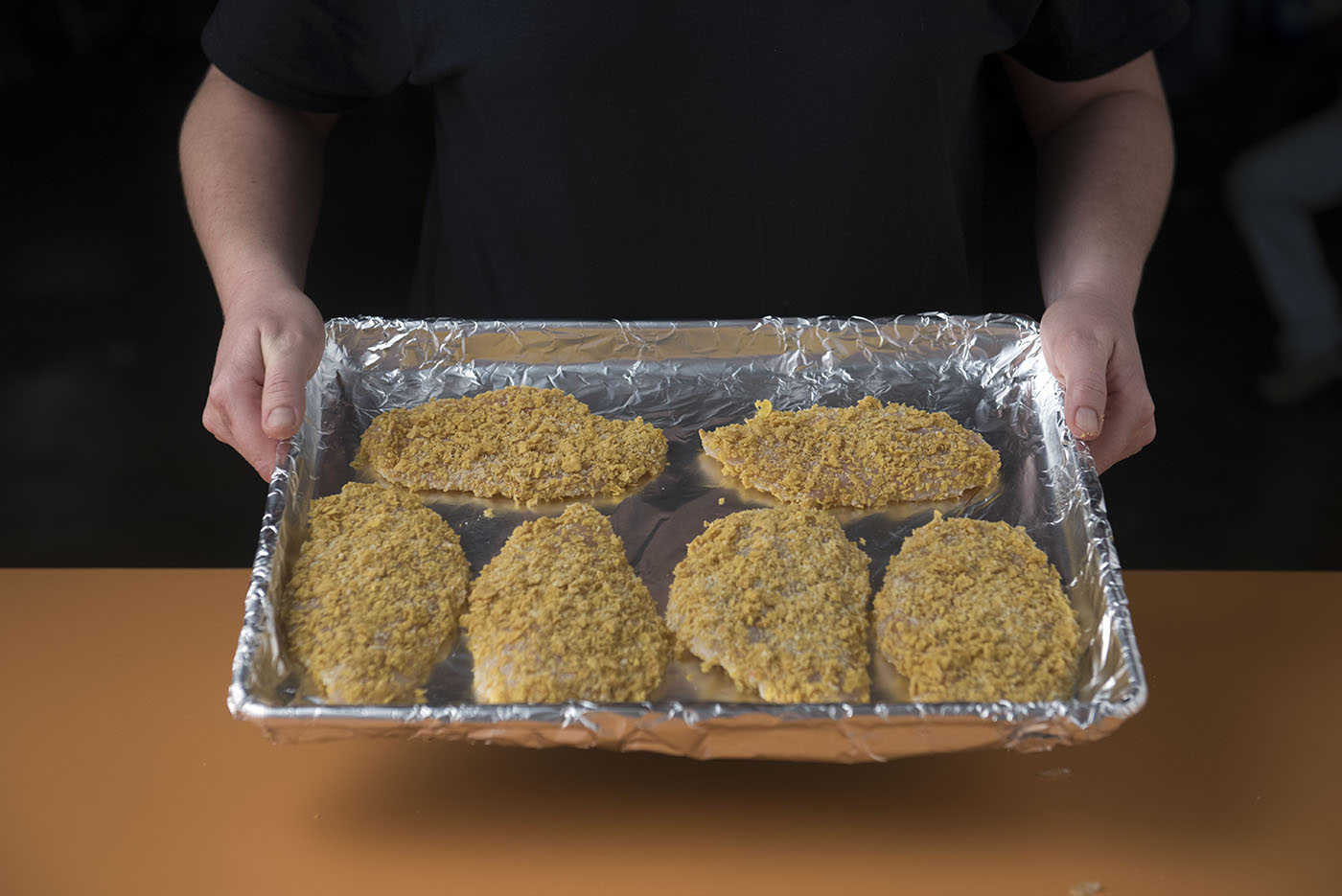 Six breaded chicken filets are on a foil-wrapped baking sheet.