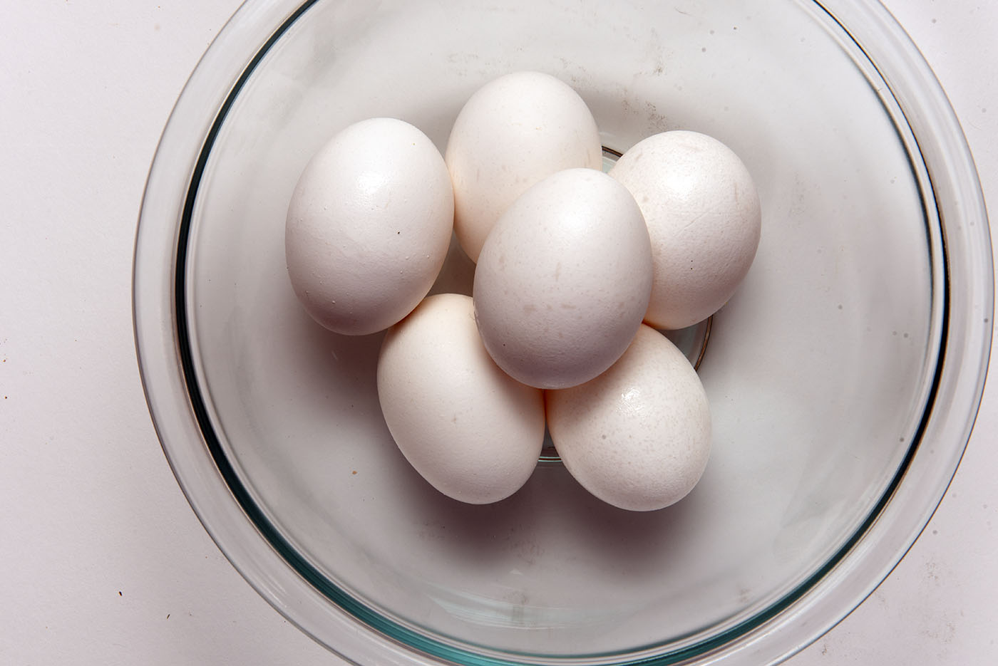 A clear glass bowl holding six boiled eggs.