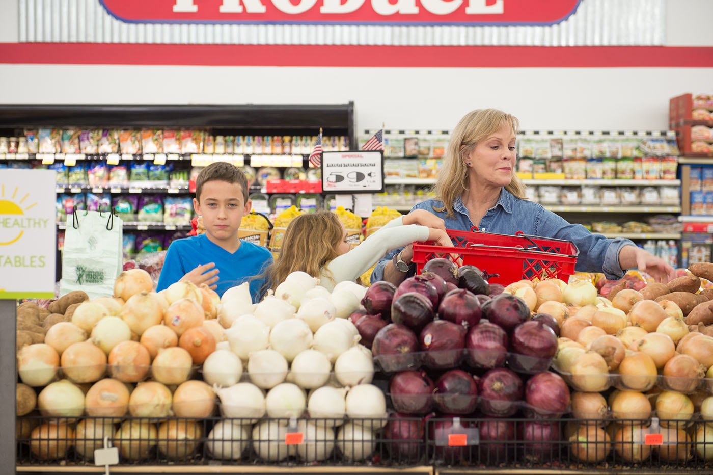 A woman and two children choose yellow, white, or red onions in a grocery store.