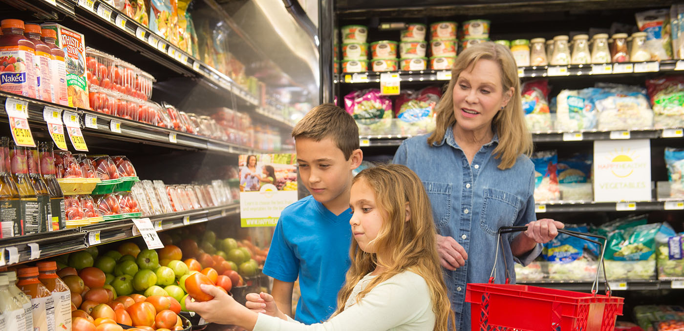 A woman, a boy, and a girl shopping for fruits and vegetables in a grocery store.