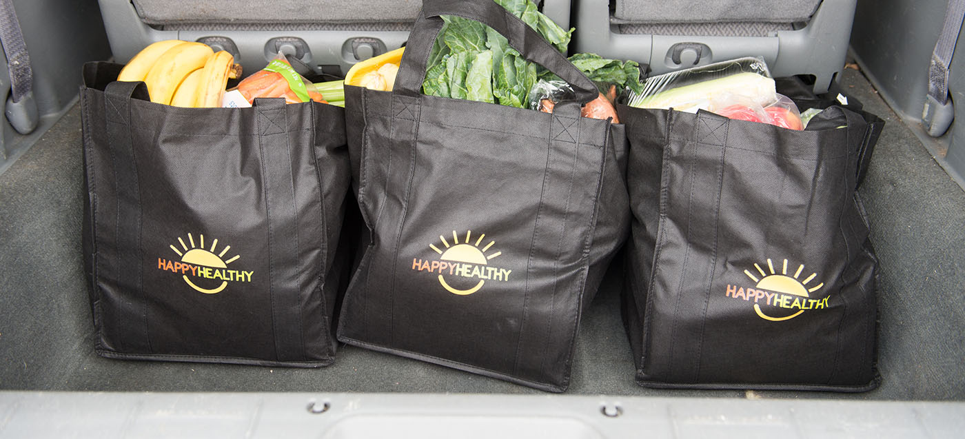 Three HappyHealthy bags, in a vehicle, are filled with healthy fruits, vegetables, and meat products.