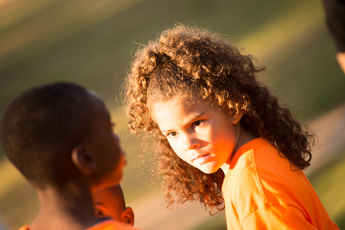A young girl, with brown hair and eyes wearing an orange tshirt, is looking at a boy.