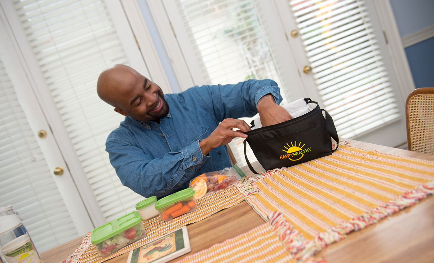 A smiling man, sitting at a table, removing his healthy lunch from a HappyHealthy lunch box.