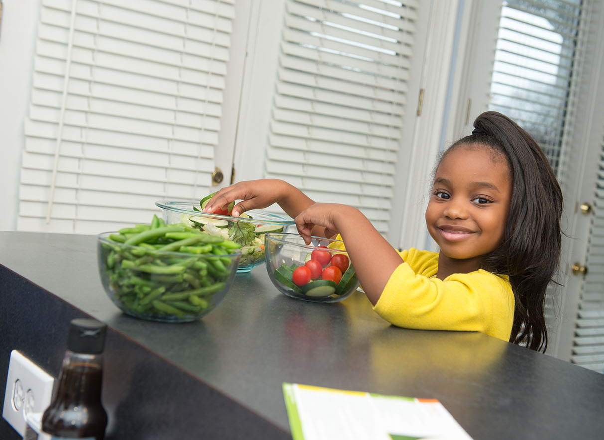 A smiling girl adds cherry tomatoes and sliced cucumbers to a larger bowl of salad greens. Snapped green beans are in a clear glass bowl are nearby.