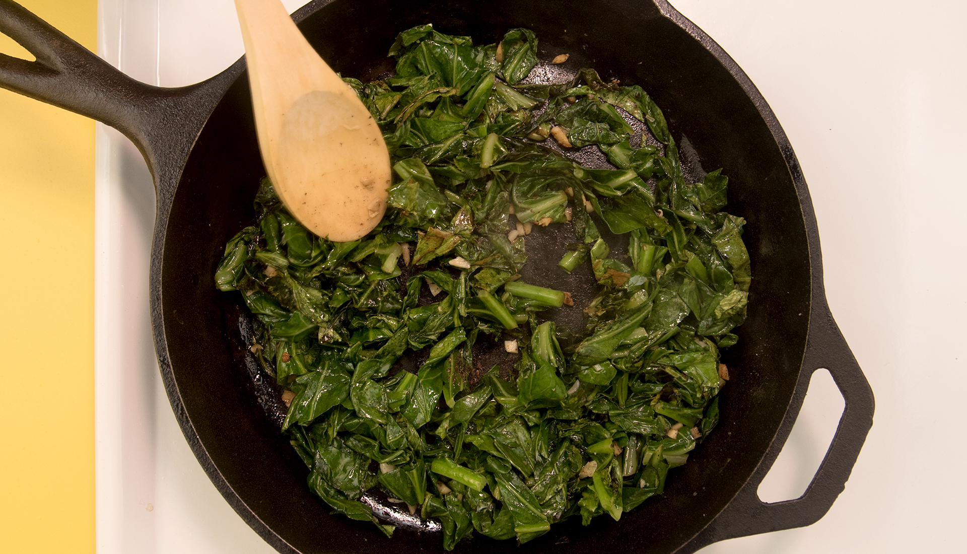 wooden spoon stirring greens in cast iron skillet on stove