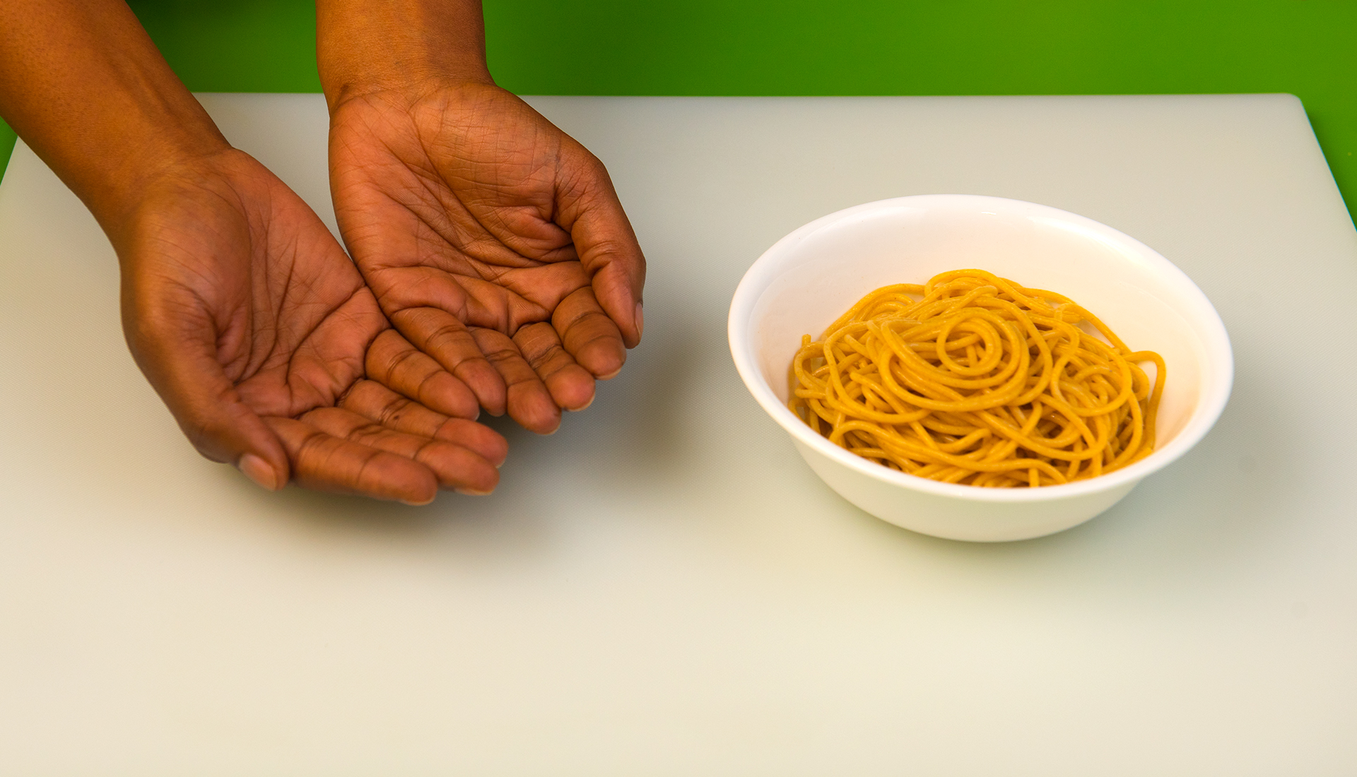 two open hands palm up beside a bowl of spaghetti noodles