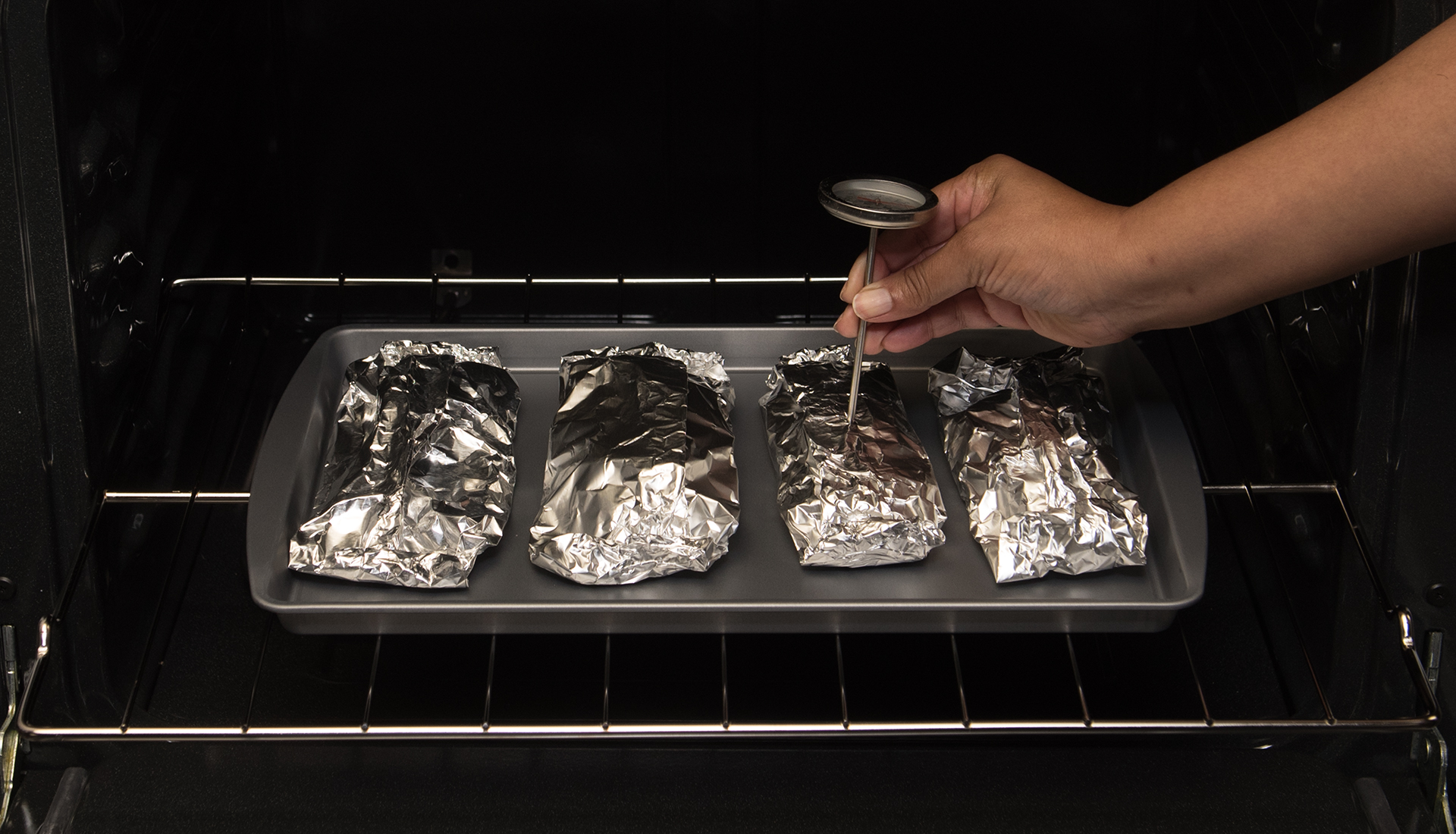 Hand with meat thermometer checking one of four foil-wrapped pieces of meat on baking sheet in oven