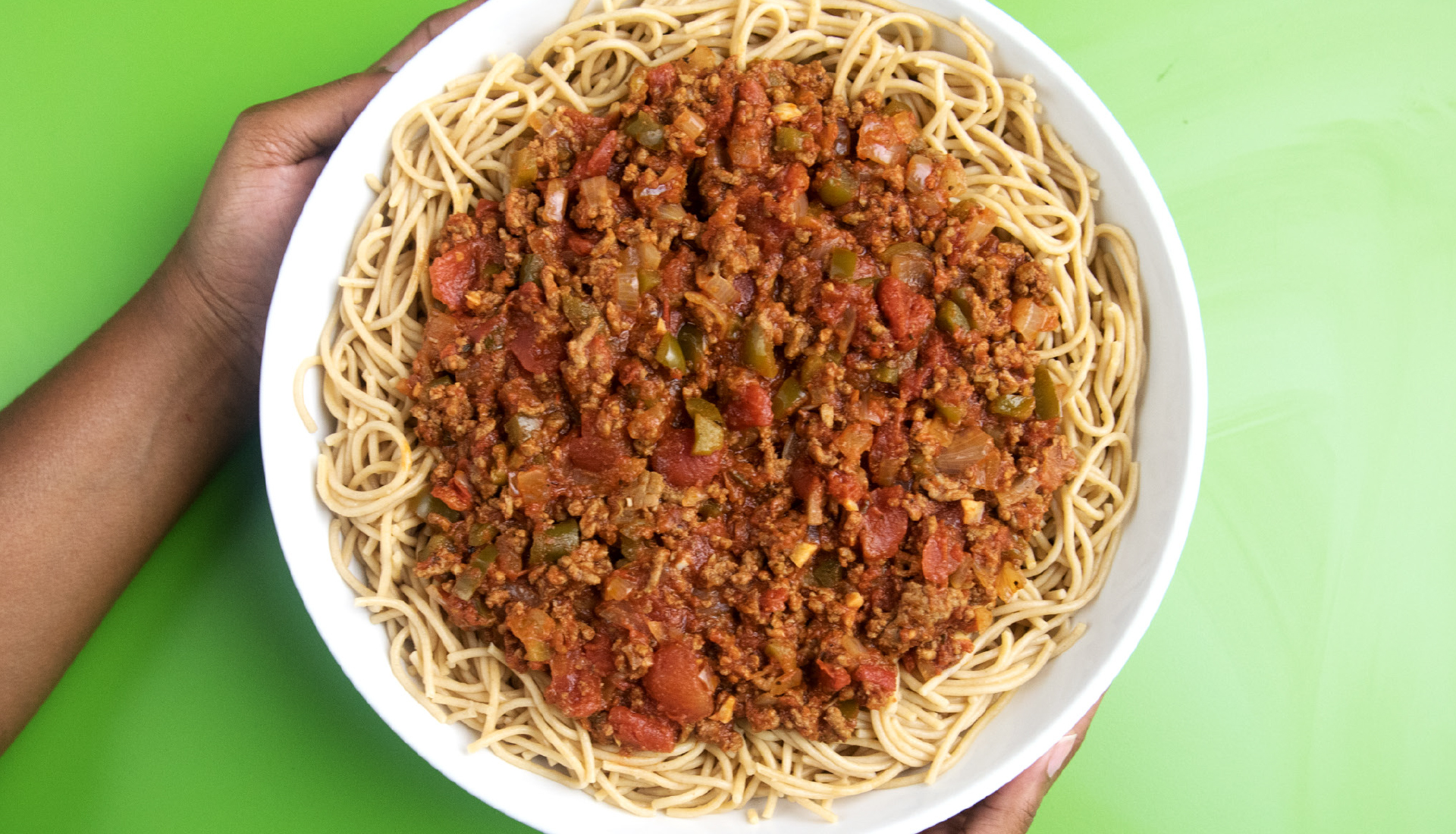 Hands presenting bowl of spaghetti topped with tomato and meat sauce