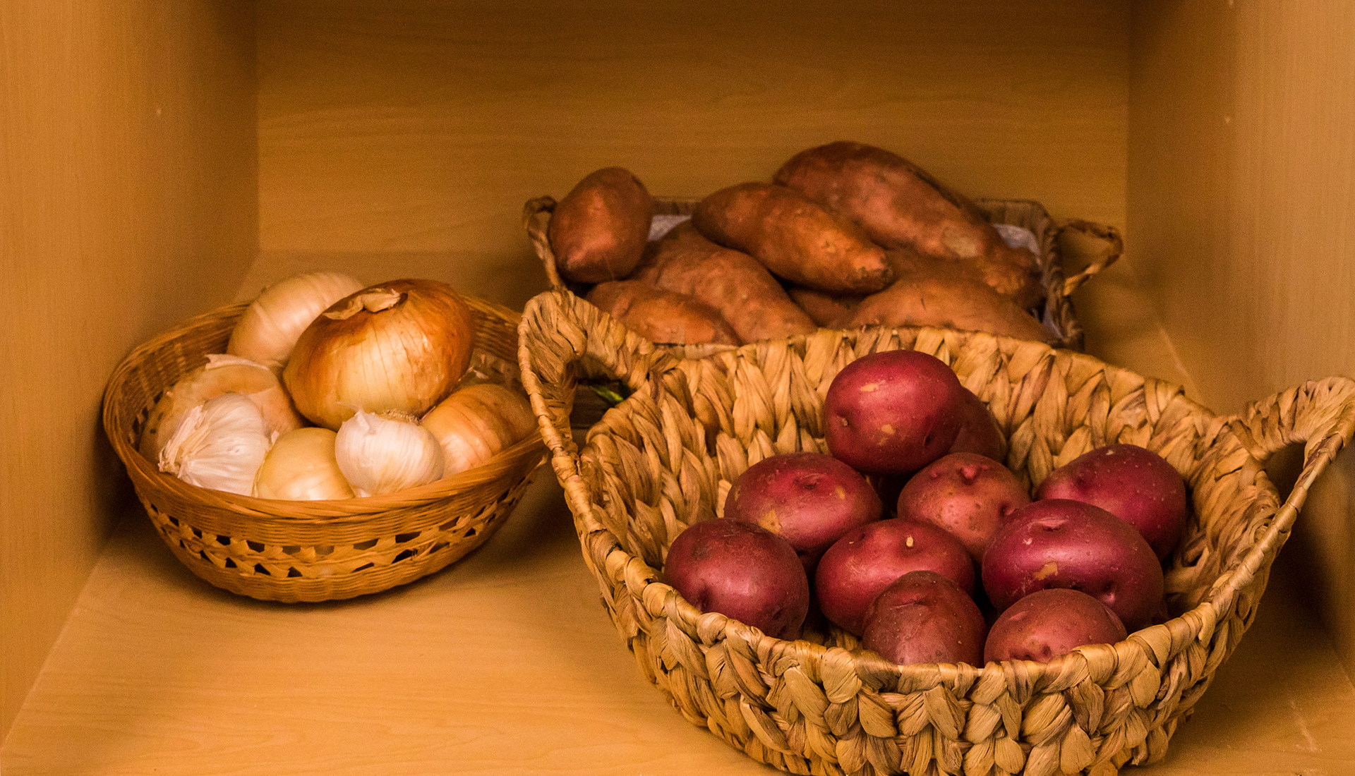 baskets of onions and potatoes in pantry.