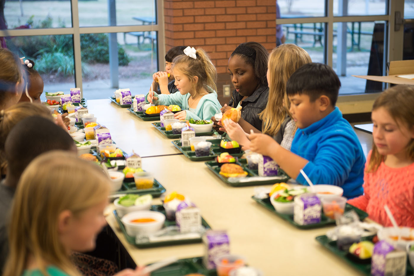 Children sitting at a lunchroom table and eating from their trays of healthy foods.