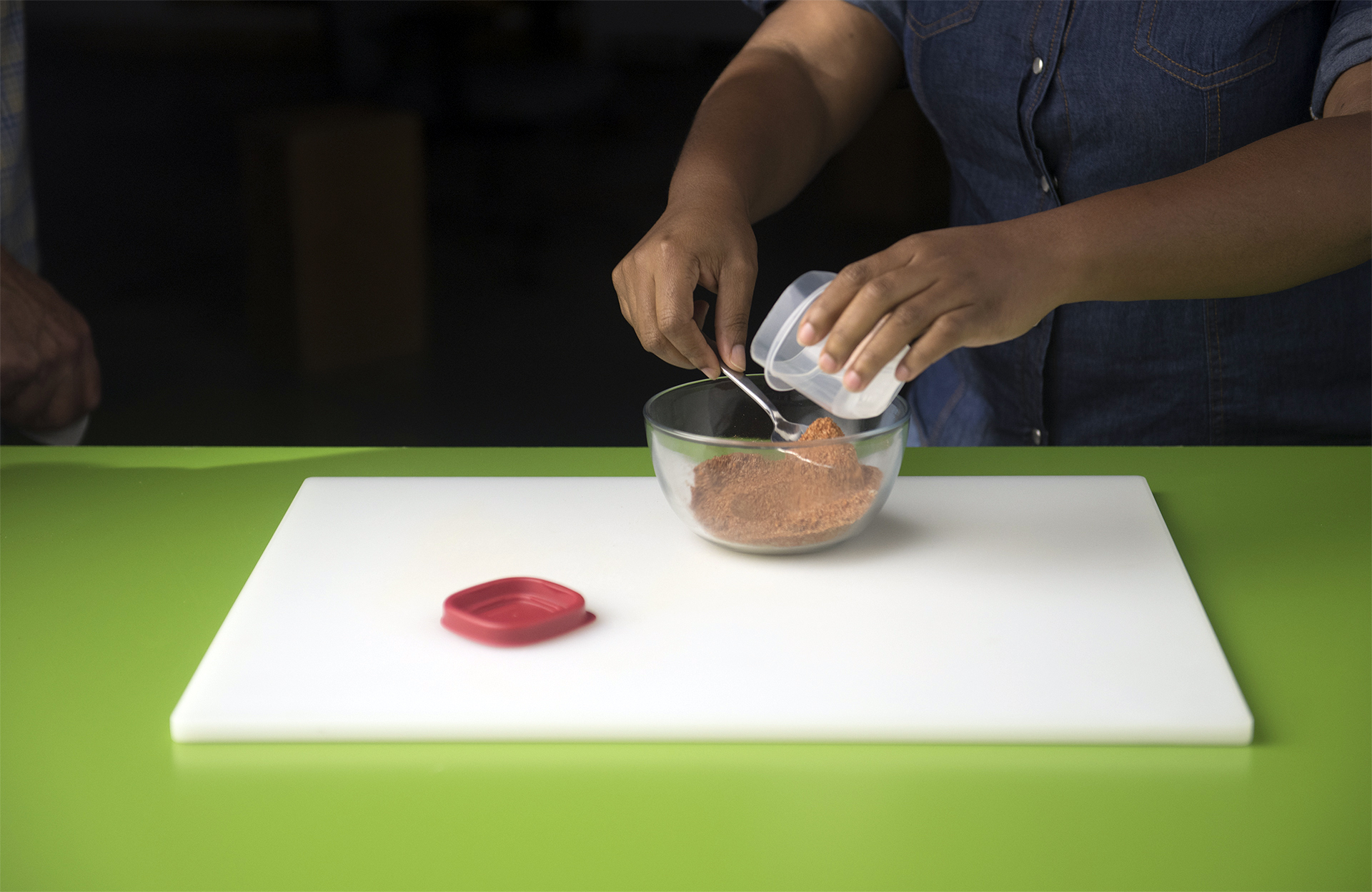 A woman places seasonings in a clear bowl on a white cutting board to prepare the all purpose seasoning.