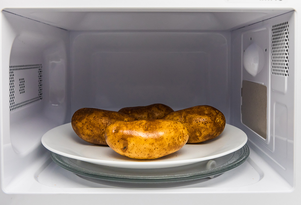 4 potatoes on white plate in microwave.