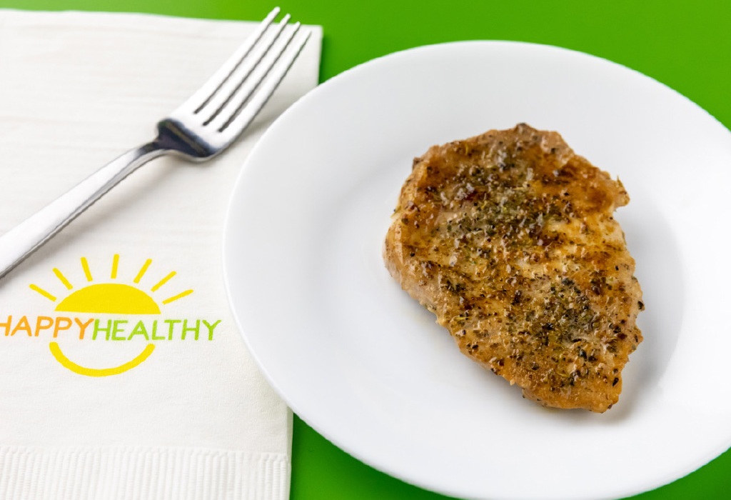 Baked Pork Chop on white plate next to white HappyHealthy napkin and fork