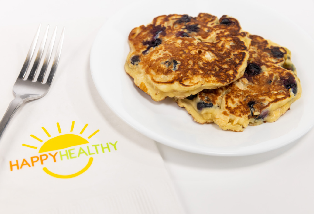 A white plate of blueberry oatmeal pancake next to a fork and HappyHealthy napkin