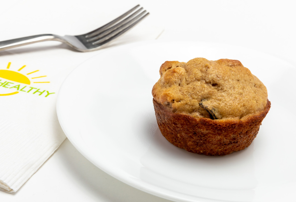 Bran muffin on white circle plate next to HappyHealthy napkin and fork