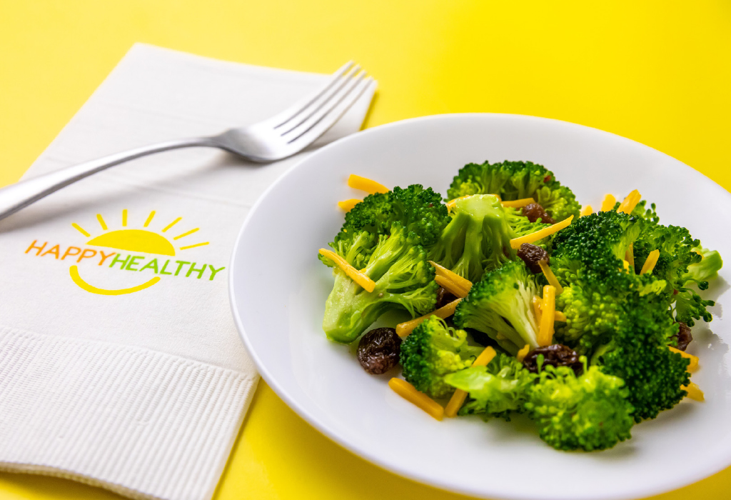 Broccoli salad on white plate next to white HappyHealthy napkin and fork.