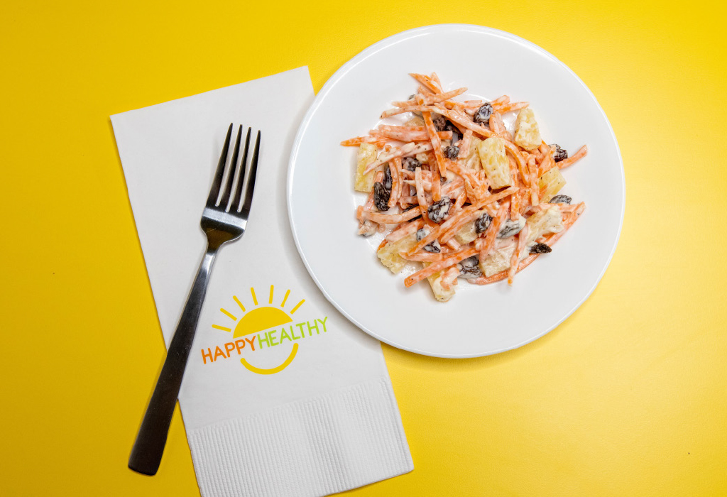 A white plate with carrot salad next to a Happy Healthy napkin and fork