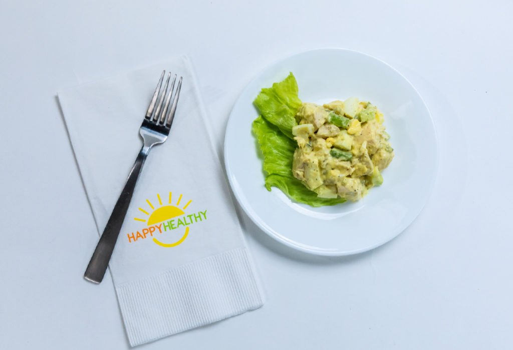 Chicken Salad on a plate with a fork on a HappyHealthy napkin.