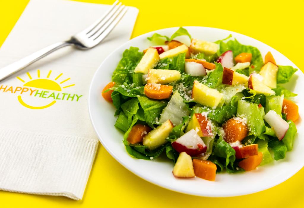 Chopped salad next to white HappyHealthy napkin with fork.