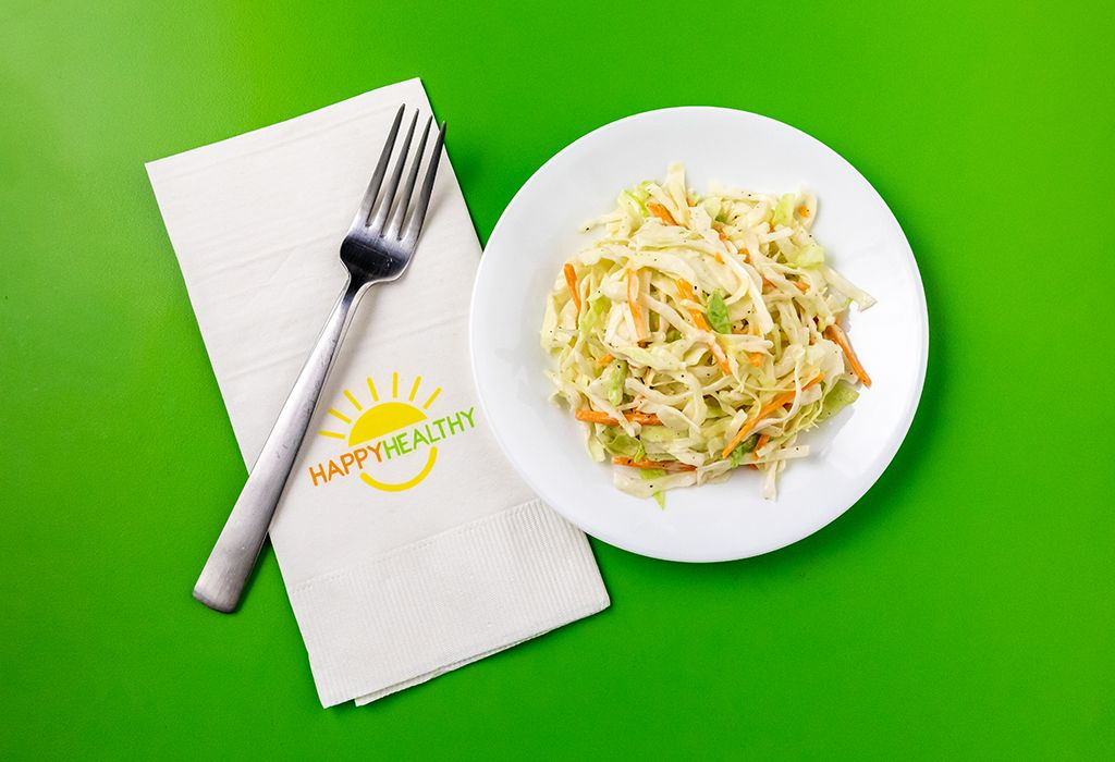 Coleslaw on a white plate with HappyHealthy napkin and fork to the left side.