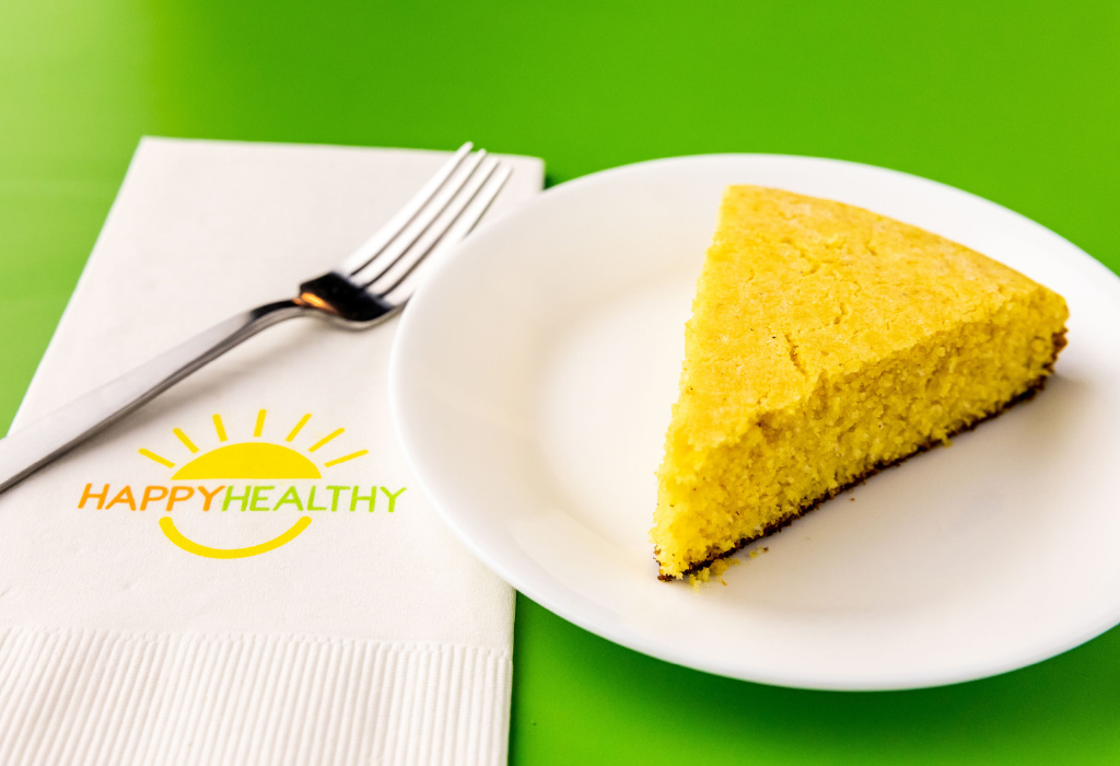 A white plate with a wedge of cornbread next to a fork and Happy Healthy napkin