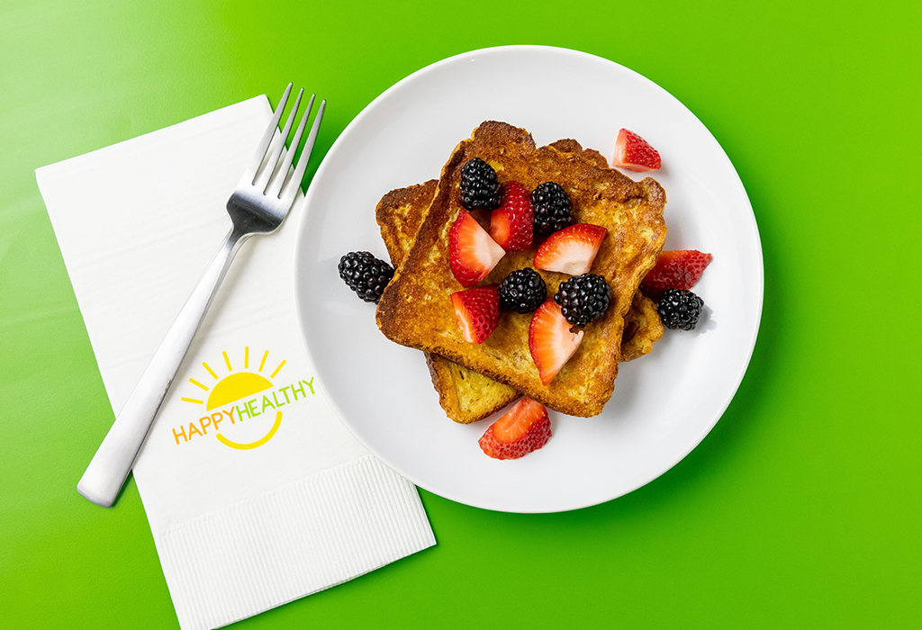 French toast topped with blackberries and raspberries on a white plate next to a Happy Healthy Napkin and Fork