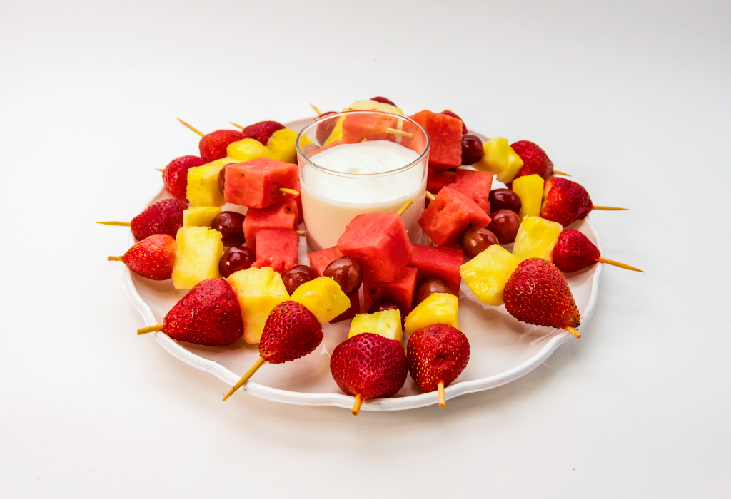 platter with chunks of fresh fruit on toothpicks and container of vanilla yogurt
