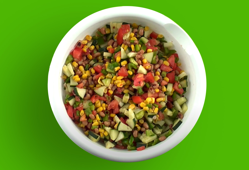 White bowl of chopped vegetables (corn, tomato, cucumber, etc) with green background.