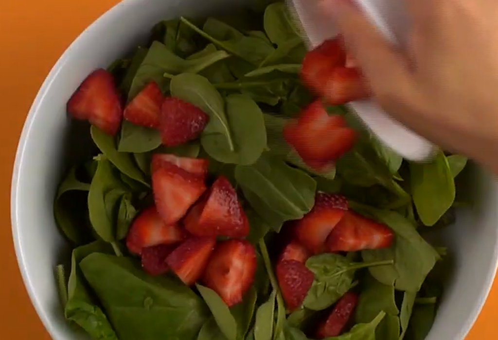 A hand adding chopped strawberries to a bowl of spinach