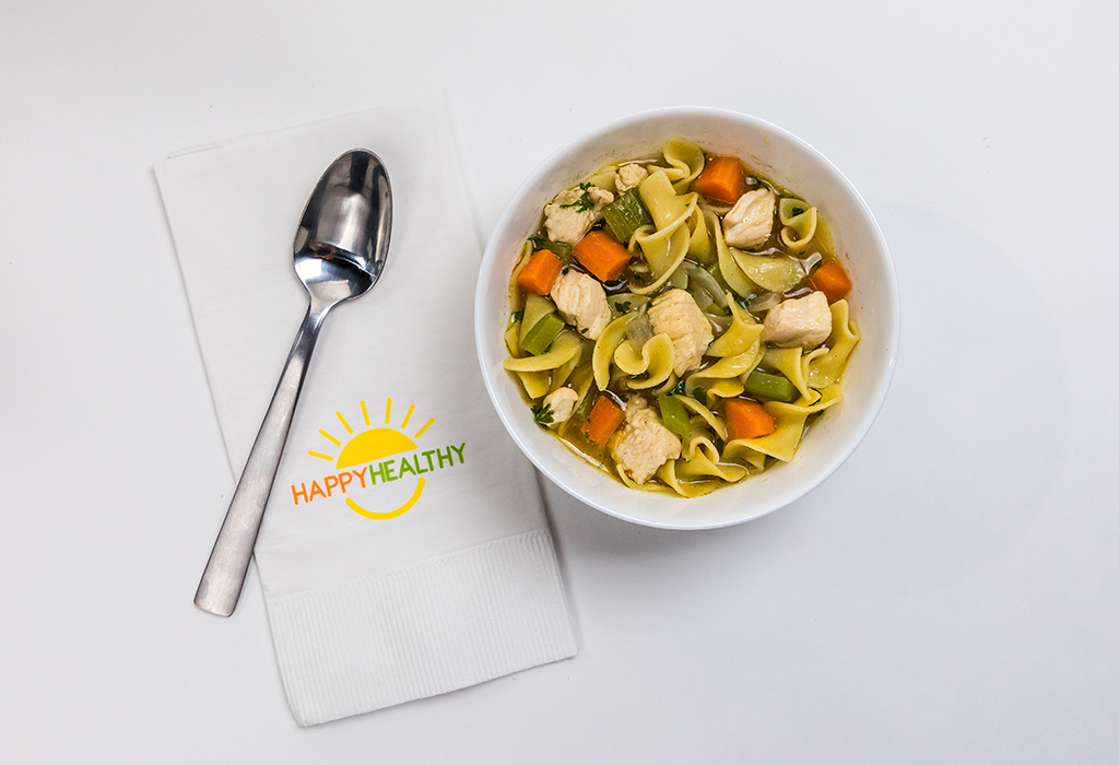 Bowl of soup with a spoon on a HappyHealthy napkin.