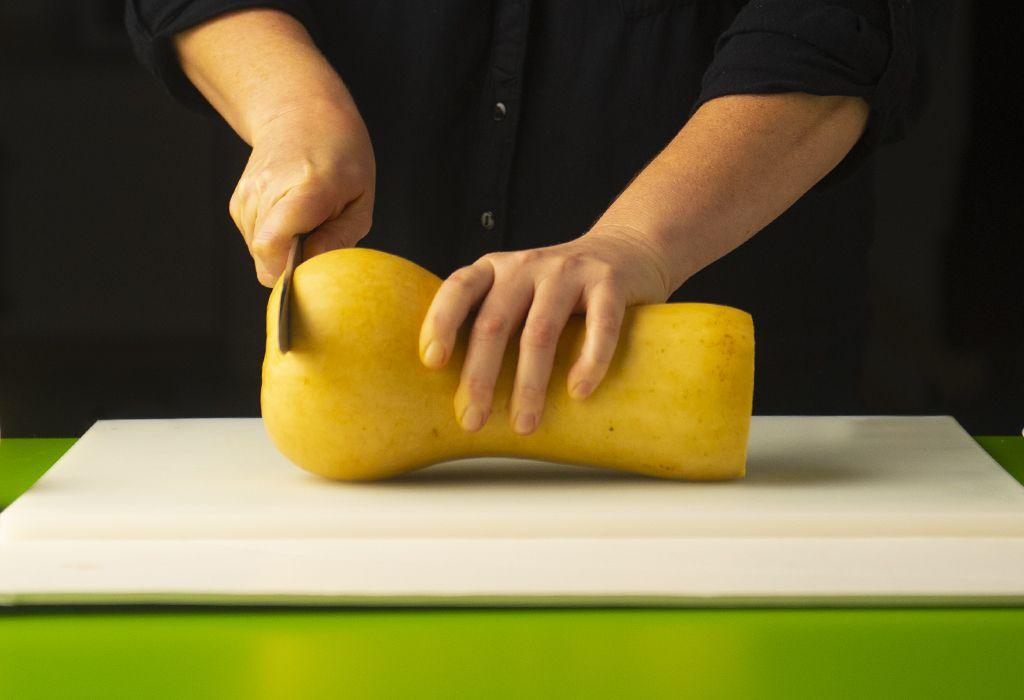 Woman cutting winter squash on a cutting board.