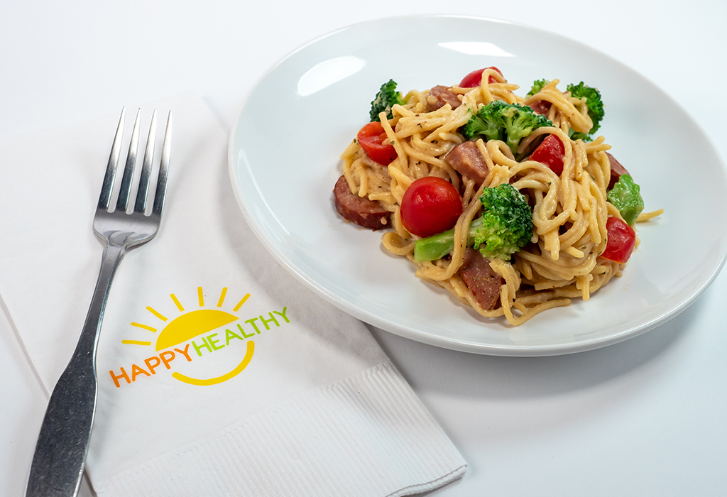A small bowl of pasta with broccoli, ham and tomatoes  next to a Happy Healthy napkin and fork