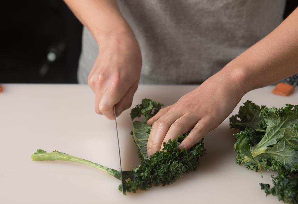 Hands using knife to cut stems off of leafy greens